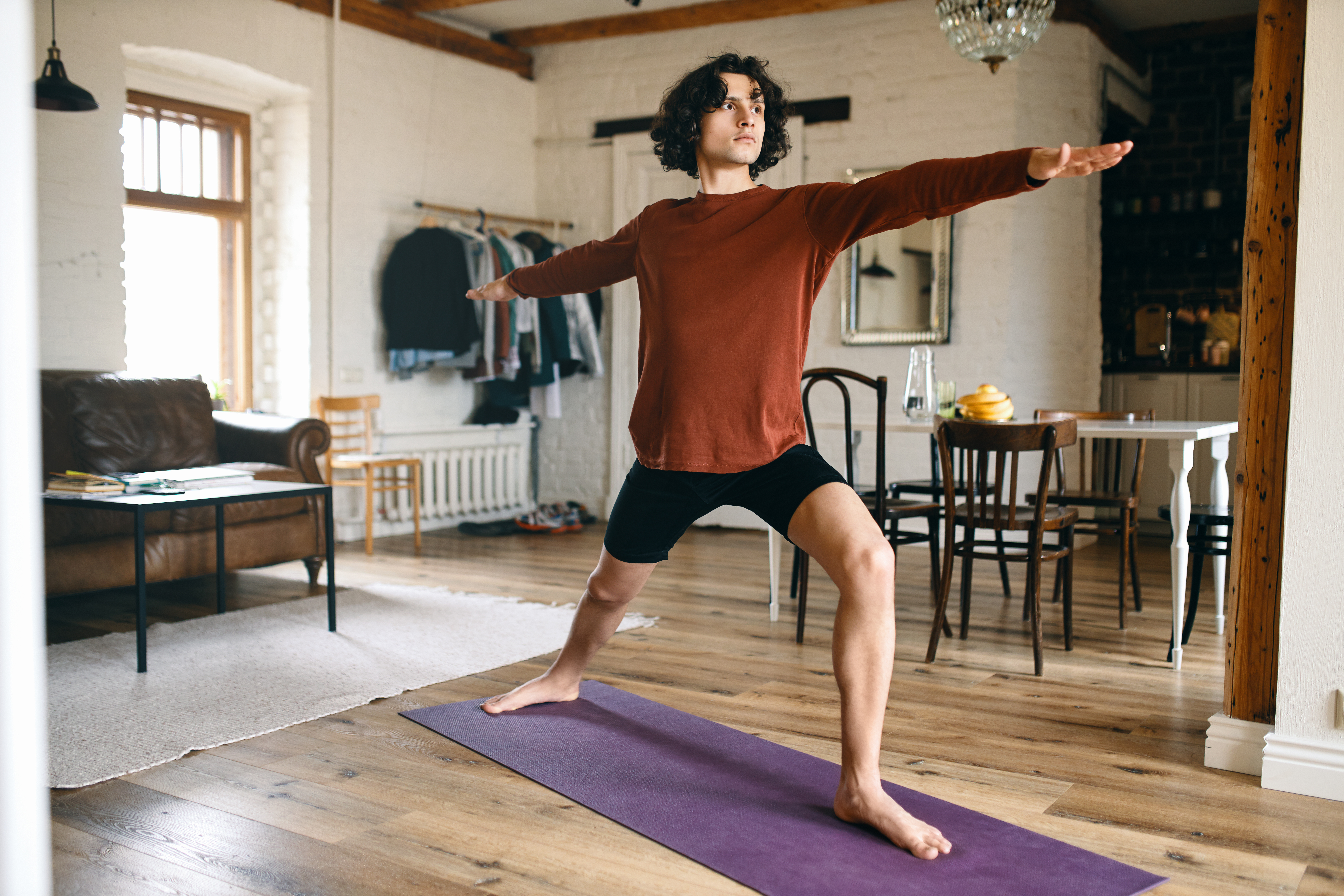 Full length image of handsome young male with strong athletic body practicing yoga indoors, standing in warrior 2 pose or virabhadrasana, taking deep breaths. Sports, active lifestyle and vitality
