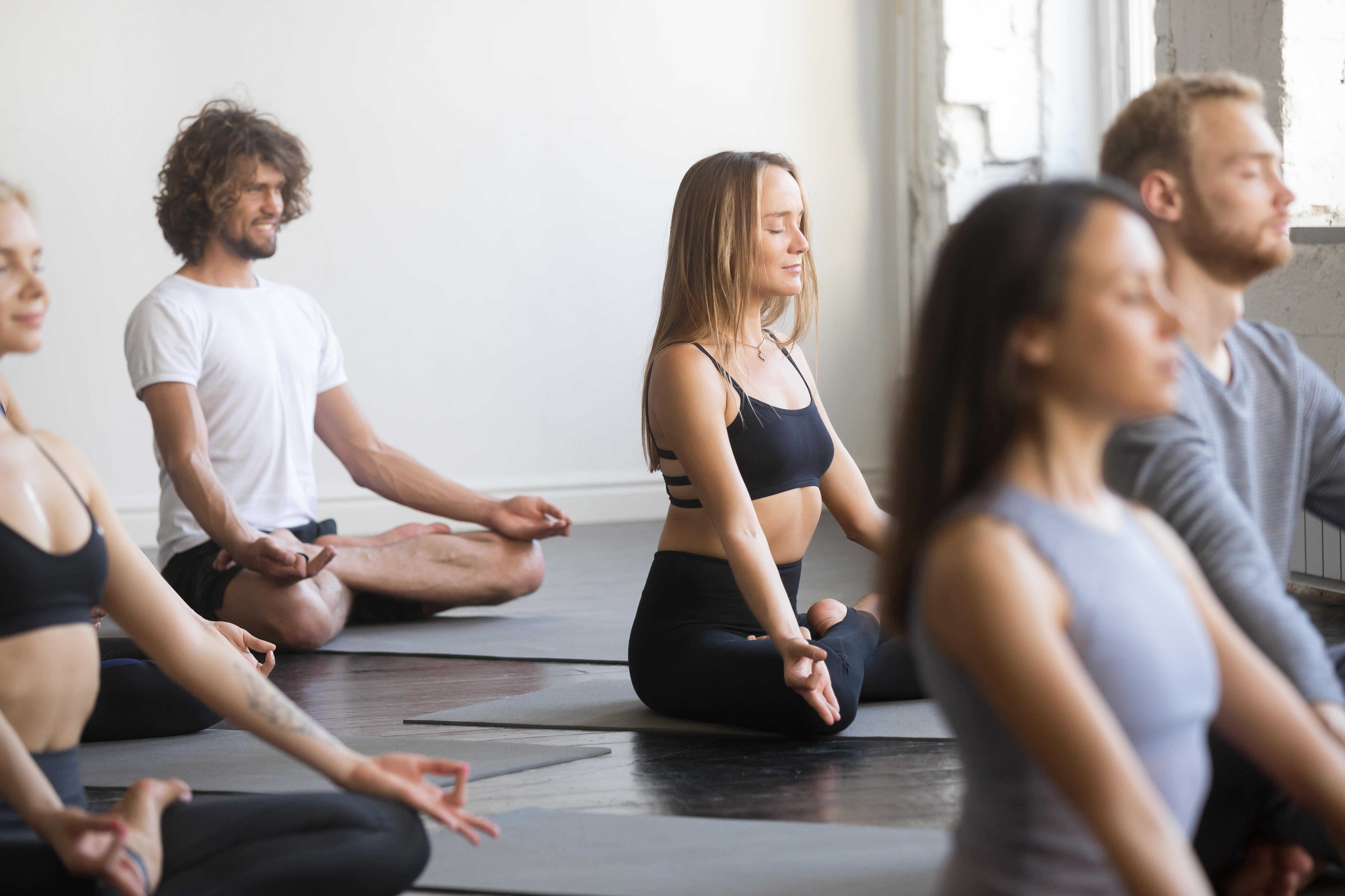 Group of young sporty people sitting in Padmasana pose