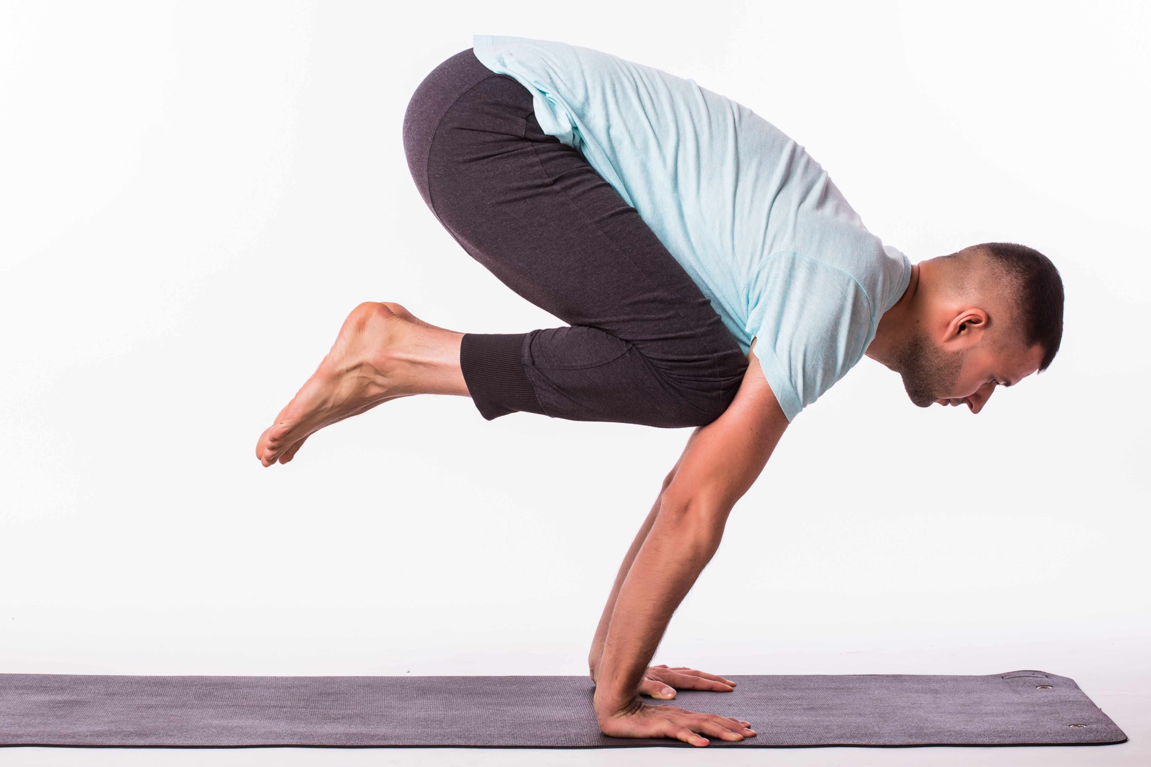 Young man is making yoga isolated over white background