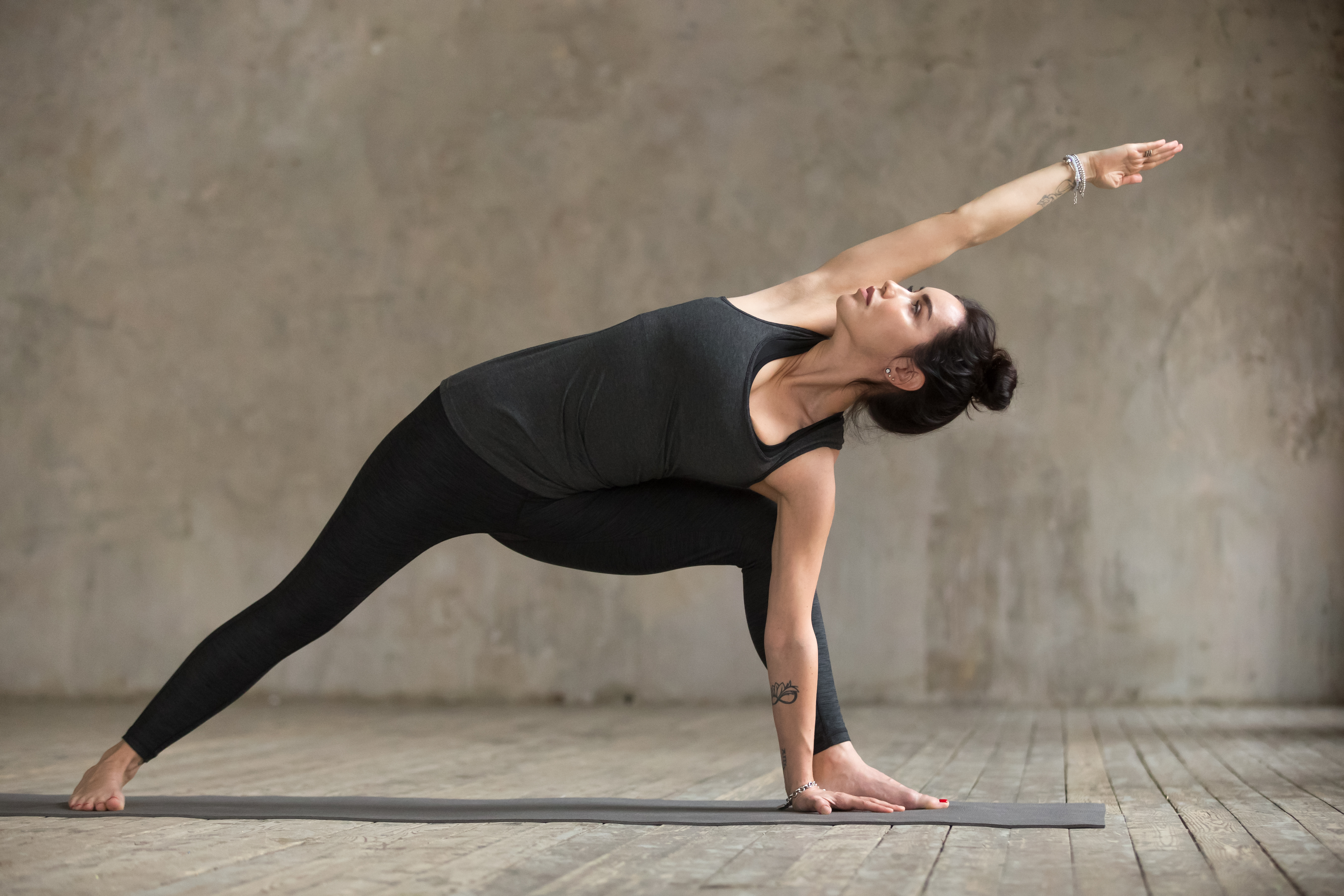 Young woman practicing yoga, doing Utthita parsvakonasana exercise, Extended Side Angle pose, working out, wearing sportswear, black pants and top, indoor full length, gray wall in yoga studio